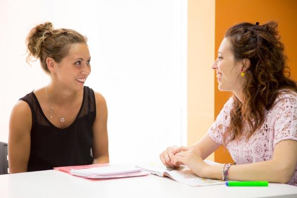 Aulas de inglês individuais no exterior, estudante eprofessora explicando gramática
